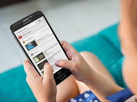 Pessoa usando smartphone na página do Youtube