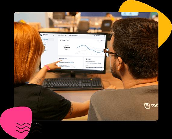 Homem e mulher olhando para gráficos no computador