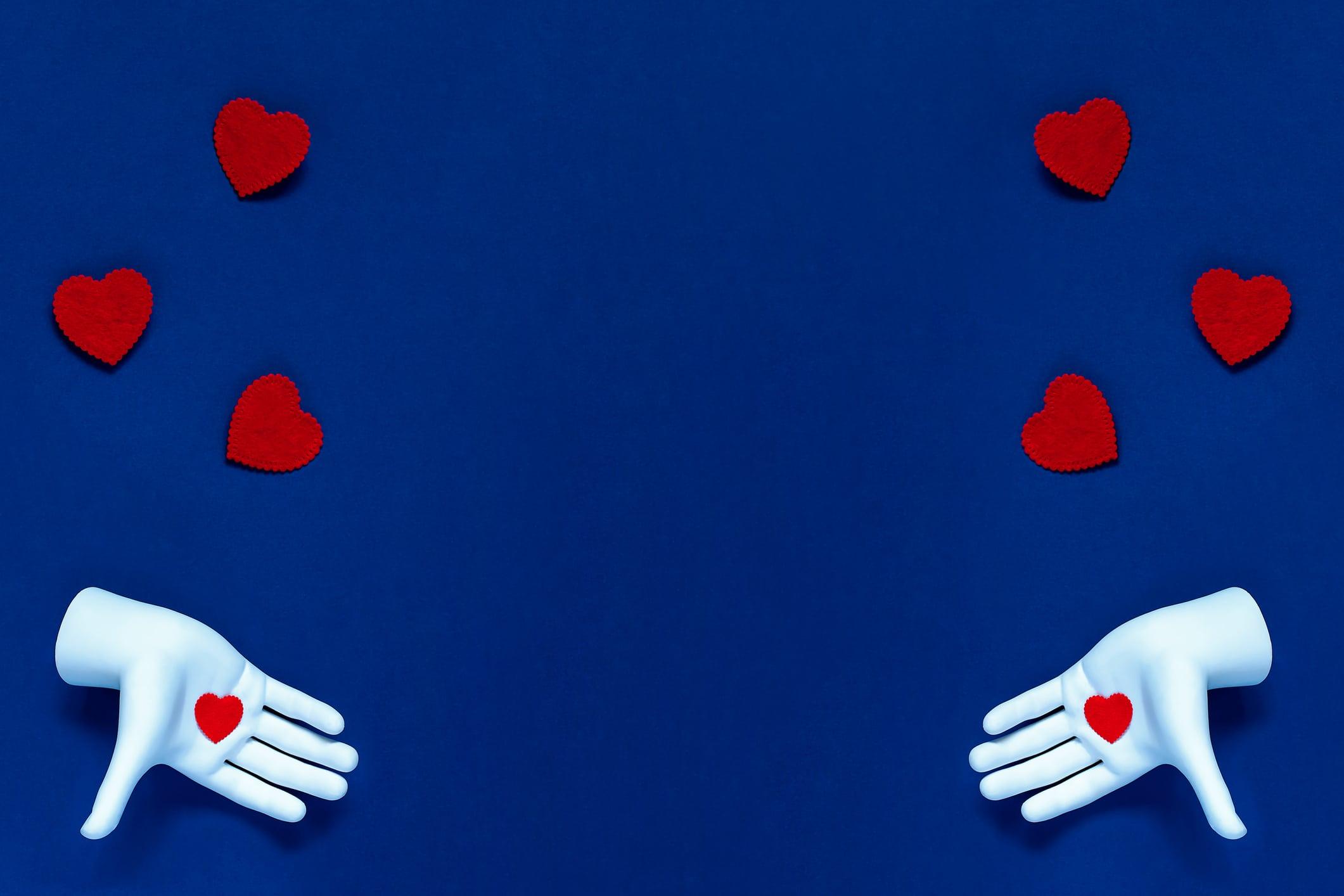 Duas mãos joando corações vermelhos ao alto