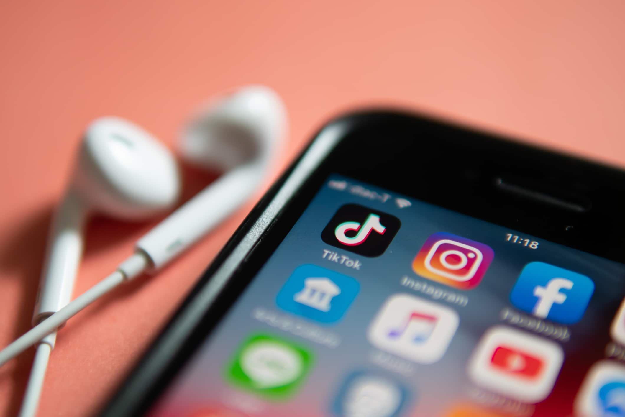 Celular ao lado de fones de ouvidos e na tela há vários aplicativos instalados e o TikTok em destaque