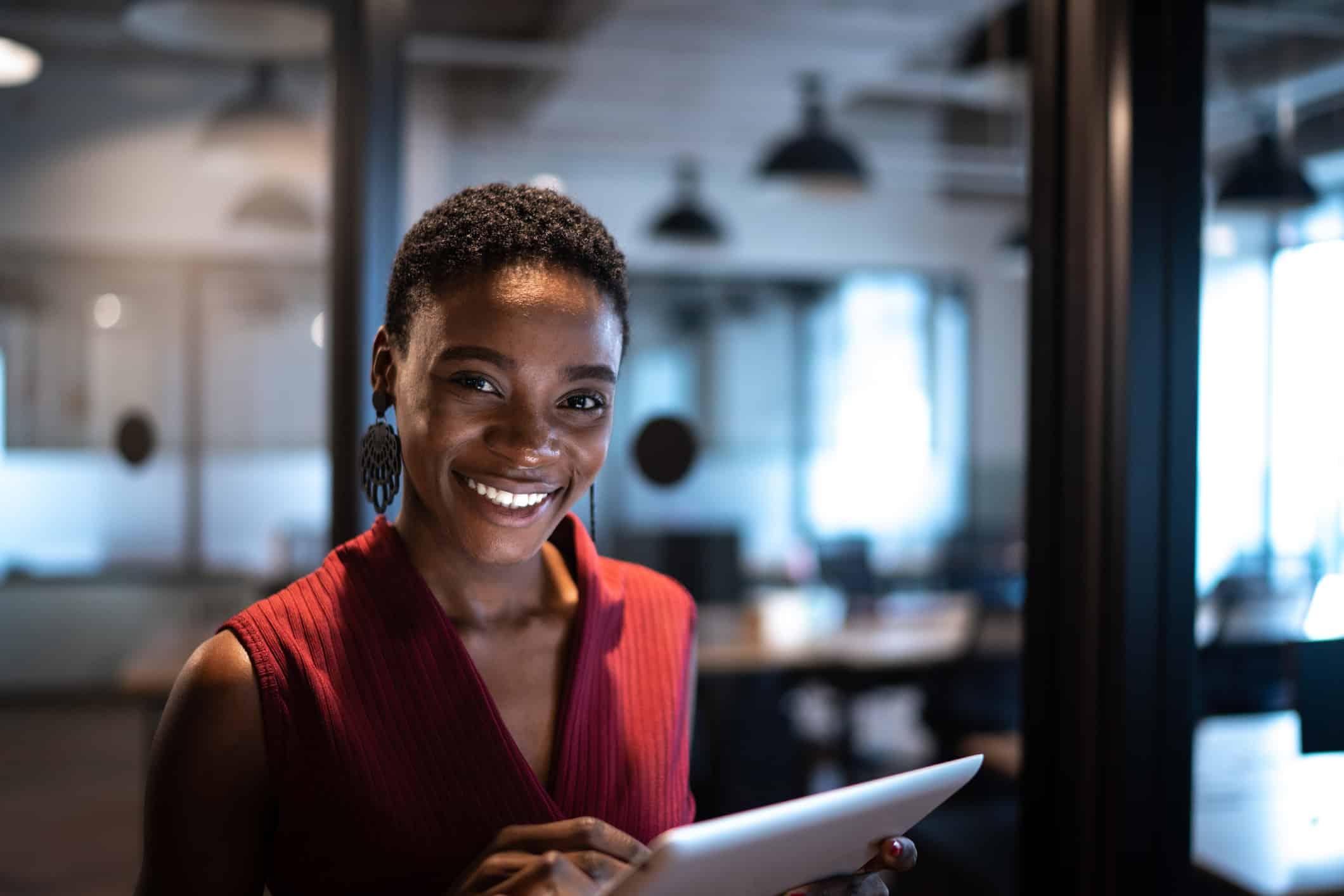 Mulher sorrindo trabalhando em um tablet