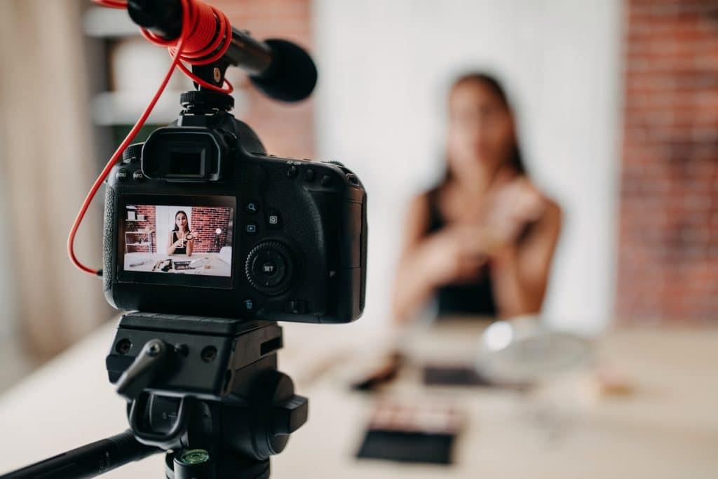 Mulher gravando um vídeo em uma câmera semi-profissional com microfone acoplado