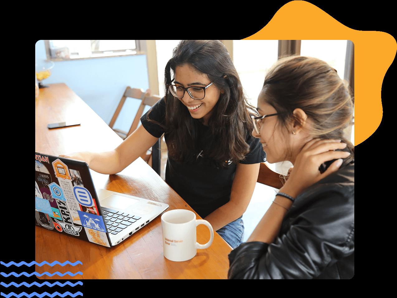 Dos mujeres jóvenes sonrientes interactúan con una experiencia de contenidos en una computadora