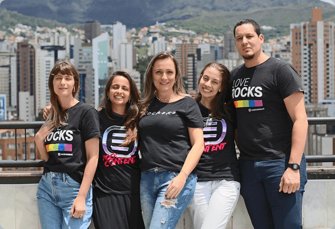 Cinco profesionales de Rock Content parados en una terraza