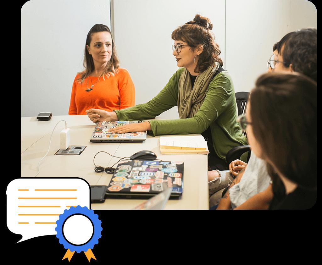 Cuatro personas en una reunión de marketing alrededor de una mesa con computadoras y cuadernos