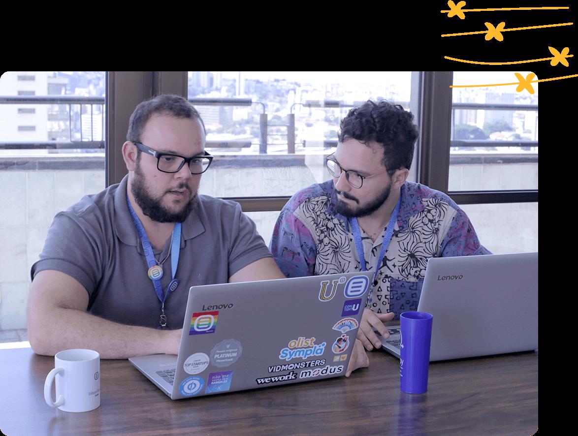 Dos profesionales de marketing de Rock Content gestionan un proyecto en sus computadoras.